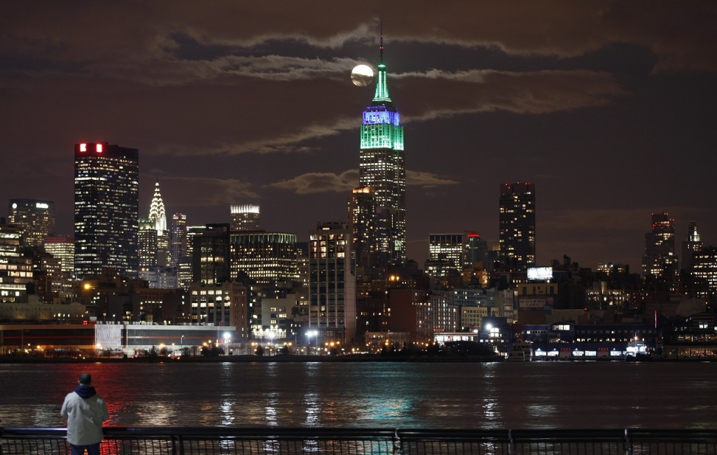 A full moon rises behind the Empire State Building in New York as a man watches in a park along the Hudson River in Hoboken, New Jersey, February 25, 2013. REUTERS/Gary Hershorn (UNITED STATES - Tags: CITYSCAPE) - RTR3EAKB